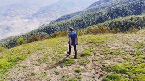 Ung handelsresande som ser sikt av naturen i Sapa Vietnam i regnig s?song man i bergen som ser in i avst?ndet arkivfilmer
