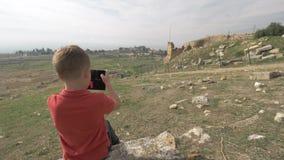 Ung handelsresande som tar bilder av Hierapolis, forntida stad i Pamukkale kalkon arkivfilmer