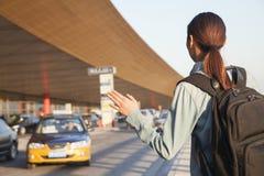Ung handelsresande som välkomnar en taxi på flygplatsen royaltyfria bilder