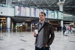 Ung handelsresandeman med kaffekoppen på flygplatsen överbord av avvikelser och ankomster royaltyfria bilder