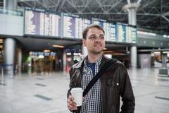 Ung handelsresandeman med kaffekoppen på flygplatsen överbord av avvikelser och ankomster royaltyfri fotografi