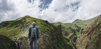 Ung handelsresandeman som överst står av den Cliff In Mountains And Enjoying sikten av naturen, bakre sikt arkivfoton