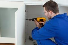Ung handyman som fixar en dörr royaltyfria foton