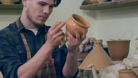Ung hantverkaredanandeundersökning av lerakrukan lager videofilmer