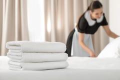 Ung hembiträde som gör säng i hotellrum, fokus på bunt royaltyfri bild