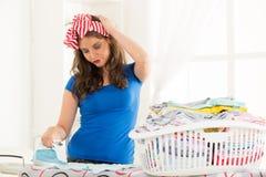 Ung hemmafru Ironing The Laundry Arkivbild