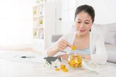 Ung hemmafru som använder insättningasken som sparar det guld- myntet Royaltyfria Bilder