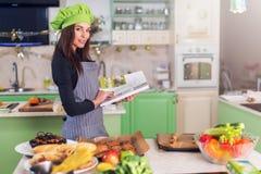 Ung hemmafru som försöker att finna ett nytt recept i kokbok, medan stå på tabellen med mat och ingredienser royaltyfri foto