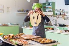 Ung hemmafru som har den roliga hållande roliga degframsidan, medan baka bakelse i köket Royaltyfri Fotografi