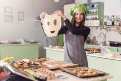 Ung hemmafru som har den roliga hållande roliga degframsidan, medan baka bakelse i köket Arkivbild