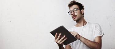Ung hipster med den digitala minnestavlan Royaltyfria Foton