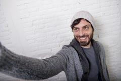 Ung hipsterbloggerman som är hållande av bild eller videoen för selfie för skärmmobiltelefonskytte royaltyfria foton