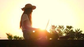 Ung Hipsterflicka i Straw Hat Sitting på stranden och maskinskrivningen på bärbar datortangentbordet med härlig tropisk solnedgån stock video
