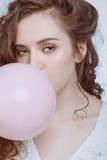 Ung hipsterflicka som blåser bubbelgum på vit Royaltyfria Bilder