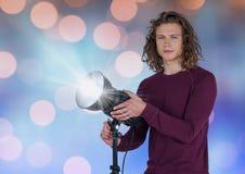 Ung hipsterfotograf med facklan Blå och orange bokehbakgrund royaltyfri bild