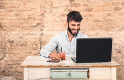 Ung hipstergrabb med mustaschsammanträde på bärbara datorn Arkivfoton