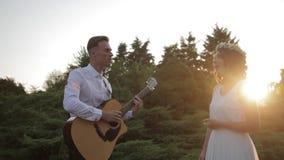 Ung hipstergrupp av vänner som tycker om som spelar tillsammans gitarren och sjunger på solnedgång lager videofilmer