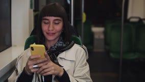Ung hipsterkvinna som använder smartphonen som offentligt sitter transport, steadicamskott Den unga kvinnan mottar på goda nyhete lager videofilmer