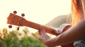Ung Hipsterkvinna som spelar ukulelegitarren på den härliga tropiska strandsolnedgången 4K thailand stock video