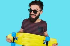 Ung hipsterman med en skateboard royaltyfria foton