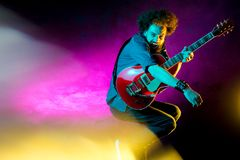 Ung hipsterman med hopp f?r lockigt h?r med den r?da gitarren i neonljus leka rock skjuten studio f?r elektrisk gitarrmusiker royaltyfri bild
