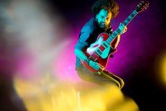 Ung hipsterman med hopp f?r lockigt h?r med den r?da gitarren i neonljus leka rock skjuten studio f?r elektrisk gitarrmusiker arkivbild