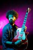 Ung hipsterman med lockigt h?r med den r?da gitarren i neonljus leka rock skjuten studio f?r elektrisk gitarrmusiker arkivfoto