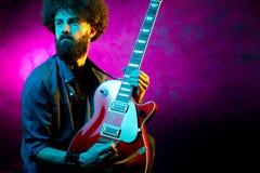 Ung hipsterman med lockigt h?r med den r?da gitarren i neonljus leka rock skjuten studio f?r elektrisk gitarrmusiker arkivbilder