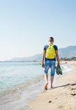 Ung hipsterman som barfota promenerar den havskusten och stranden med hans gymnastikskor i hand Arkivbild