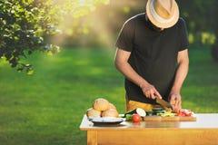Ung hipsterman som förbereder mat för det trädgårds- gallerpartiet, sommargrillfest arkivfoton