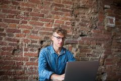 Ung hipstermanmaskinskrivning på bärbar datordatoren, sammanträde mot tegelstenväggen i Co-arbete utrymme royaltyfri fotografi