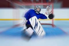 Ung hockeygoalie som fångar en flygpuck Royaltyfria Bilder