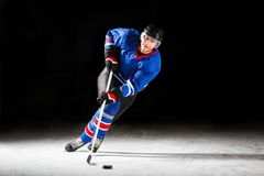Ung hockeyspelare som åker skridskor på isbana i attack Arkivbilder