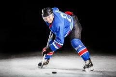 Ung hockeyspelare som åker skridskor på isbana i attack Royaltyfri Fotografi
