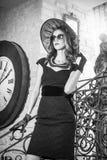 Ung härlig brunettkvinna i svart anseende på trappa nära en over storleksanpassad väggklocka Elegant romantisk mystisk dam Royaltyfri Foto