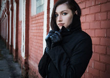 Ung härlig fundersam flicka nära tegelstenväggen Arkivbild
