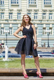 Ung härlig kvinna i den svarta klänningen som utomhus poserar i soligt oss Royaltyfria Foton