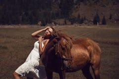 Ung härlig kvinna i den vita klänningen som går med hästen Arkivfoton