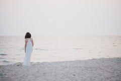 Ung härlig kvinna i en vit klänning som går på en tom strand nära havet Fotografering för Bildbyråer