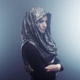 Ung härlig kvinna i stilfull udde med huven Stående på mörk bakgrund, rök och dimma Arkivbild