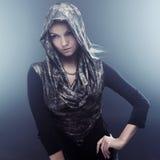 Ung härlig kvinna i stilfull udde med huven Stående på mörk bakgrund, rök och dimma Royaltyfri Fotografi