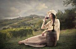 Ung härlig kvinna som dricker ett exponeringsglas av vin Royaltyfria Bilder