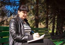 Ung härlig kvinna som skriver en penna i anteckningsbok Arkivbilder