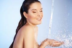 Ung härlig kvinna under strömmen av vatten Arkivbild