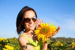 Ung härlig kvinnaflicka på bakgrund av solrosfältet Arkivfoto