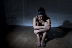 Ung härlig latinsk kvinna eller tonårigt sitta för flicka som är ledsna och som är ensamma i lättretligt mörker som känner sig de Fotografering för Bildbyråer