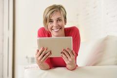 Ung härlig lycklig 30-talkvinna som ler genom att använda soffan för vardagsrum för digitalt minnestavlablock den hemmastadda Arkivfoton