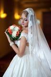 Ung härlig lyxig kvinna i bröllopsklänningen som poserar i lyxig inre Bruden med länge skyler innehavet hennes bröllopbukett Royaltyfri Fotografi
