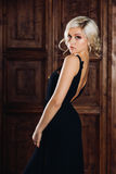 Ung härlig sexig kvinna i en lyxig lång elegant svart klänning, en moderiktig makeup och stilfulla örhängen förförisk blondin Royaltyfria Bilder