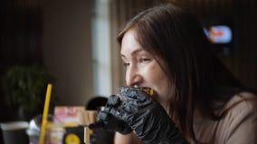 Ung hungrig flicka i svarta handskar som äter en saftig hamburgare i ett kafé lager videofilmer